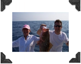 couple on a boat holding a grouper