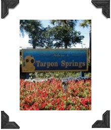 welcome to tarpon springs sign with a old fashioned diver, foreground flowers
